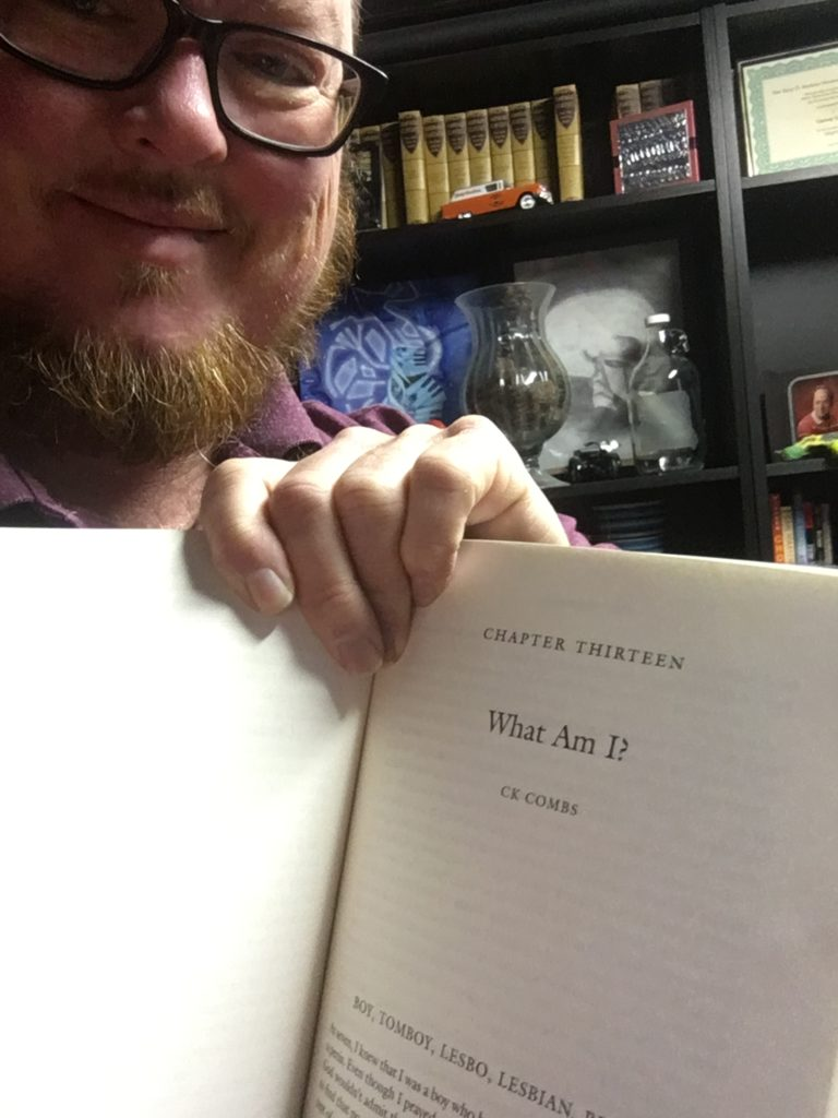 "CK Combs, aka Kyle Jones, holding up a copy of Nonbinary book showing his chapter ""What Am I?"""